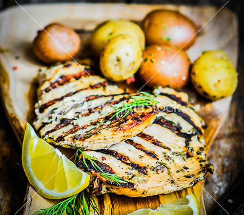 Grilled Chicken With Potatoes And Herbs On Wooden Background Stock ...