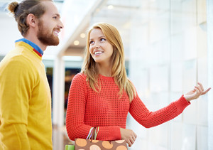 Woman Showing Something To Her Boyfriend At Shopping Window