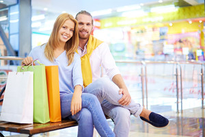 Young Couple Sitting On Bench In Shopping Mall