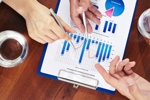 Three Business People Pointing At Paper With Marketing Analysis