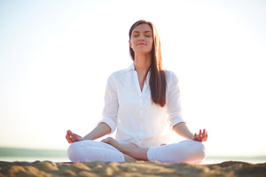 Meditating Woman Sitting In Pose Of Lotus Against Clear Sky Outdoors