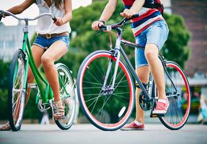 公園で自転車で男と少女の脚のクローズアップ
