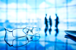 Image Of Eyeglasses At Workplace And Its Reflection With Businesspeople Standing On The Background