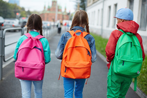 Backs Of Schoolkids With Colorful Rucksacks Moving In The Street