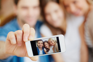 Male Hand Holding Cellular Phone With Image Of Happy Family Of Three Looking At Camera