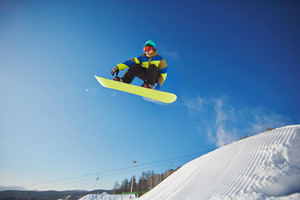 Portrait Of Sportsman Snowboarding Against Blue Sky