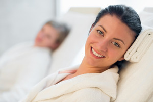 Smiling woman resting at beauty spa room friend in background