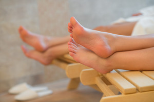 Feet of two women relaxing at beauty spa room