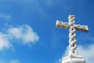 Cruz en nubes y cielo azul