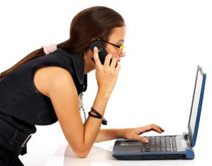 전화와 컴퓨터에 젊은 여자