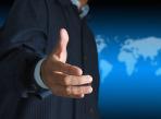 Businessman Offering For Handshake His Team On World Background